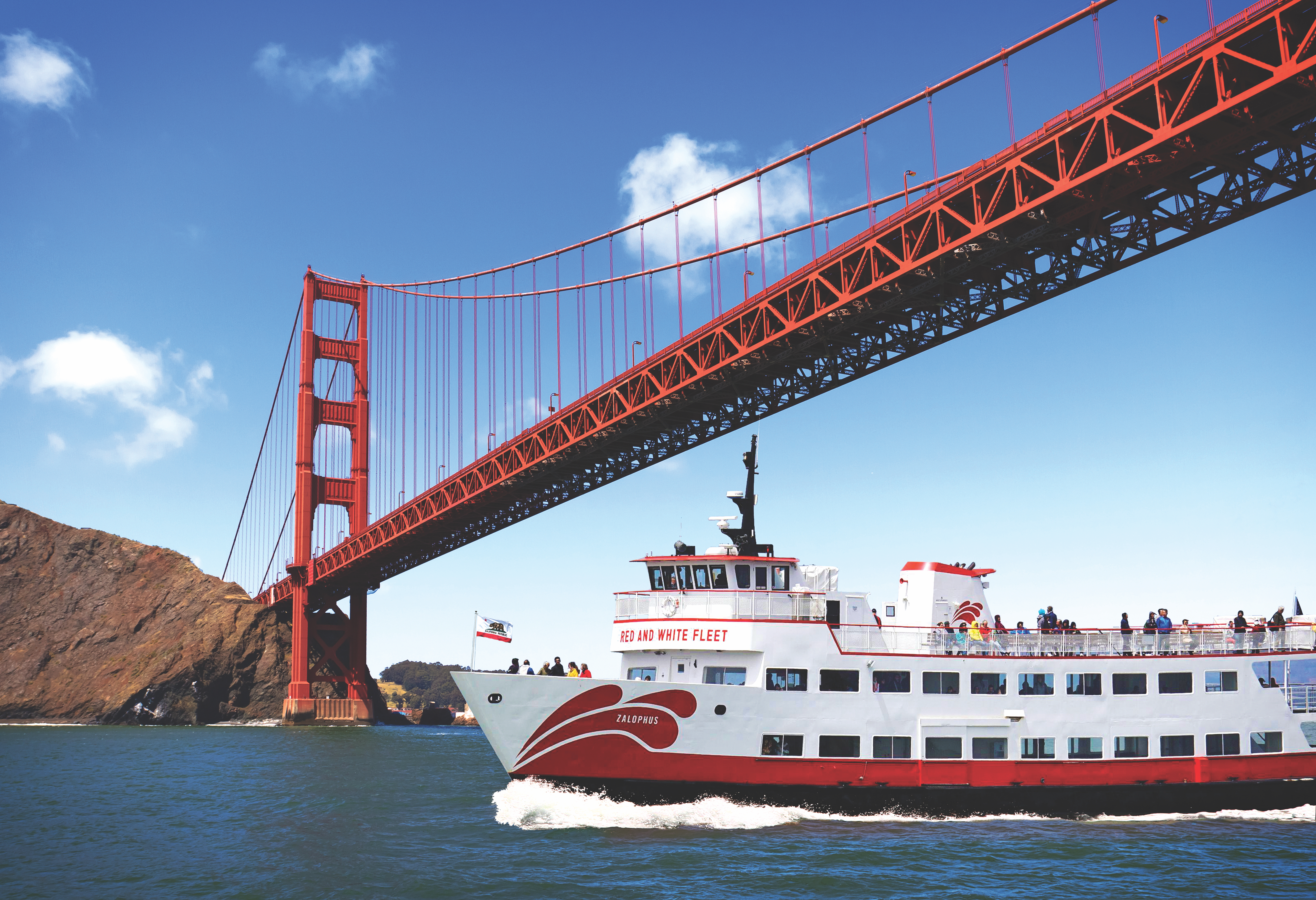 Red and White ferry traveling under the Golden Gate Bridge